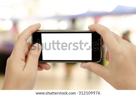 Smart phone in woman's hand on blur people background with clipping path