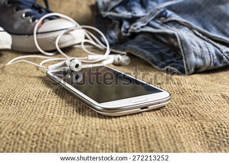 Smart phone on a table cloth with pants and sneakers. shallow depth of field. - stock photo
