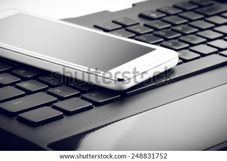 Smart Phone On Keyboard Close Up Isolated On White - stock photo
