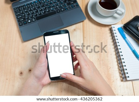 smart phone on woman hand with white blank empty screen on white desk table.