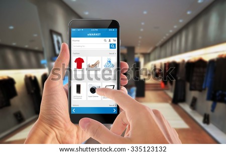 Smart phone online shopping in man hand. Shopping center in background. Buy clothes shoes accessories with e commerce web site - stock photo