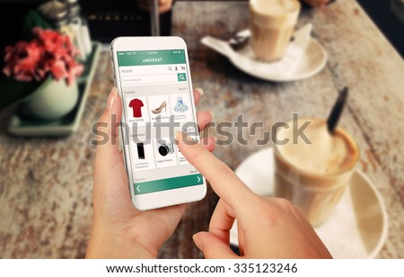 Smart phone online shopping in woman hand. Desk with caffe in background. Buy clothes shoes accessories with e commerce web site - stock photo