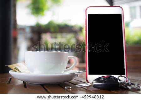 Smart phone with blank black screen and coffee cup on wooden table