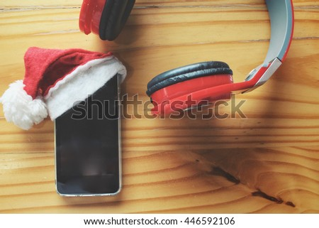 Smart phone with christmas hat and headphones