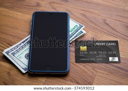 Smart phone with dollar Credit card on wooden background. Making money online