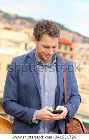 Smart phone young urban businessman on smartphone professional using smartphone using app texting sms message on smart phone wearing trendy suit jacket. Caucasian male fashion model. - stock photo