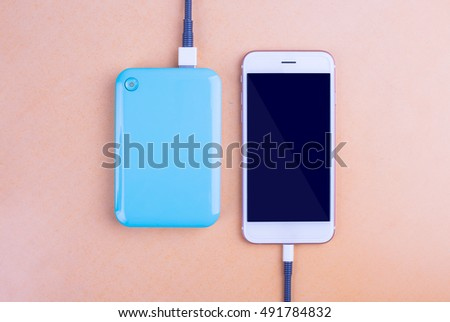 Smart phones and charging. On the table Orange background