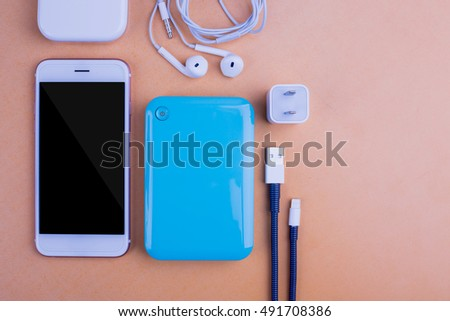 Smart phones and devices that placed on the table, background color orange.