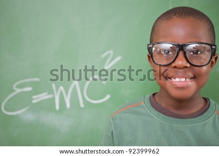 Smart schoolboy posing in front of a blackboard - stock photo