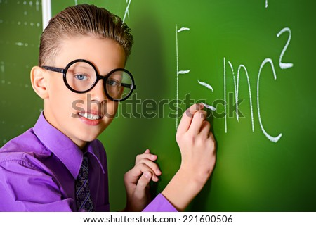 Smart schoolboy stands at the blackboard in the classroom. Education. - stock photo