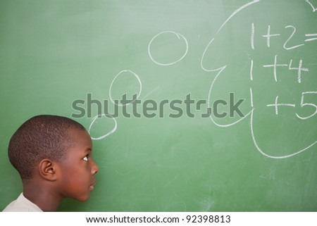 Smart schoolboy thinking about additions in front of a blackboard - stock photo