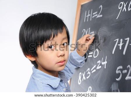 Smart schoolboy writing on blackboard - stock photo