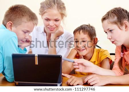 Smart schoolchildren and teacher working with netbook in class - stock photo