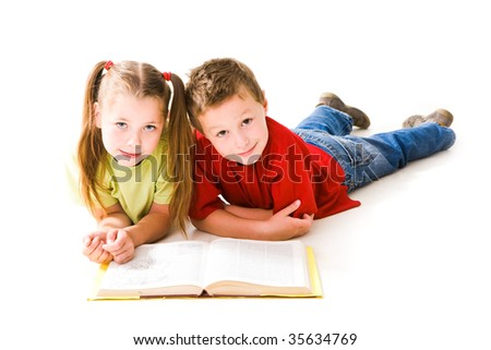 Smart schoolchildren looking at camera during reading book - stock photo