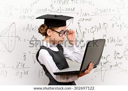 Smart schoolgirl in big glasses and academic hat performs the task at the blackboard with a laptop. Education. - stock photo
