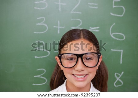 Smart schoolgirl posing in front of a blackboard - stock photo