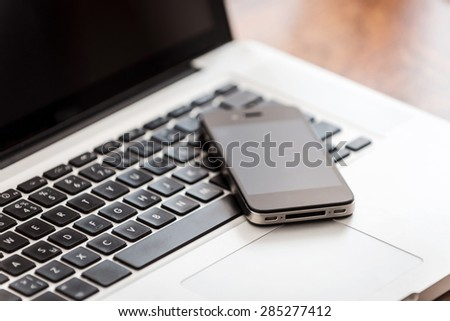 Smart technologies. Close-up of laptop with mobile phone laying on the wooden desk