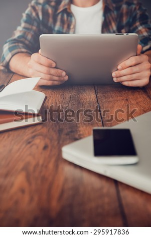 Smart technologies for successful life. Close-up of man holding digital tablet while sitting at his working place  - stock photo