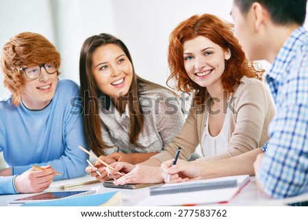 Smart teenage student looking at camera while her groupmates discussing something - stock photo