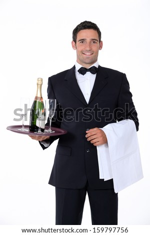 Smart waiter holding tray of champagne glasses - stock photo