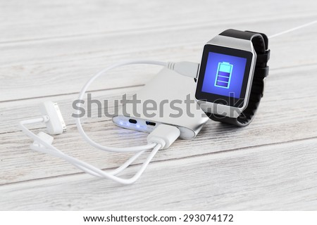 Smart watch charging with energy bank. Smartwatch concept. - stock photo