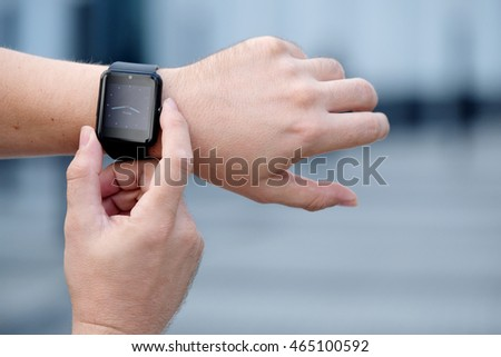 Smart watch with blank screen outdoors on urban background