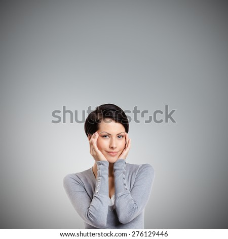 Smart woman admires her own beauty, isolated on grey - stock photo