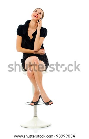 smart woman sitting on a stool holding a cellphone on white background - stock photo