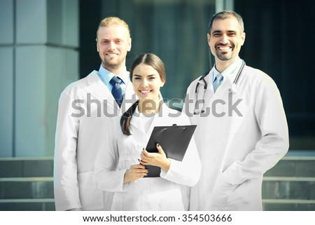 Smart young doctors team standing against hospital entrance - stock photo