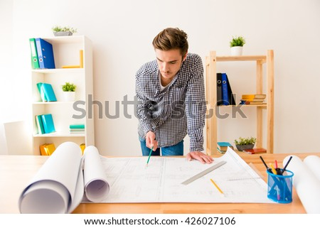 Smart young engineer drawing scheme for his  project - stock photo