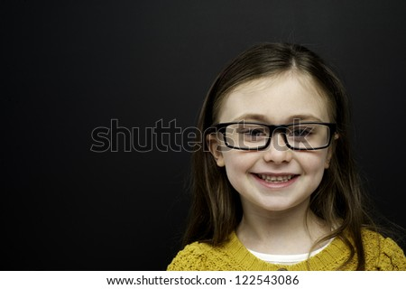 Smart young girl wearing a yellow jumper and glasses stood in front of a blackboard