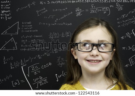 Smart young girl wearing a yellow jumper and glasses stood in front of a blackboard with mathematical equations written in chalk