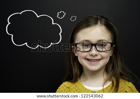 Smart young girl wearing a yellow jumper and glasses stood in front of a blackboard with a drawn on chalk thought bubble