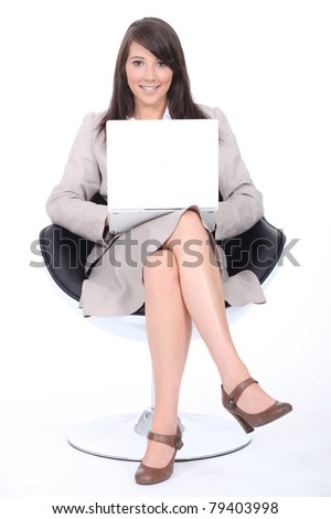 Smart young woman sitting in a swivel chair with a laptop computer - stock photo