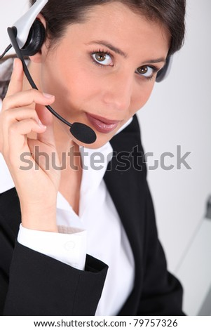 Smart young woman wearing a telephone headset - stock photo