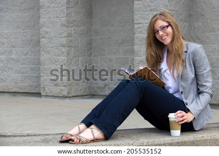 Smart young young reading her journal - stock photo