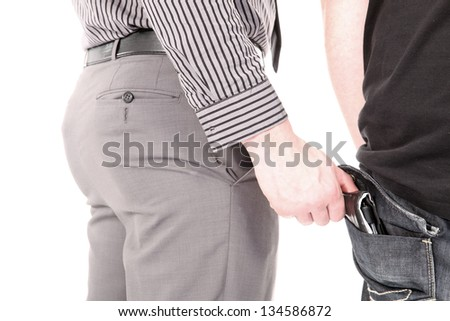 Smartly dressed male pickpocket stealing a wallet from the rear pocket of an unsuspecting victim - stock photo