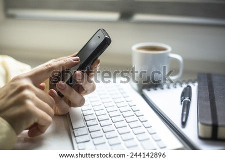 Smartphone and computer keyboard at hand, a cup of coffee and a notepad in the background. - stock photo
