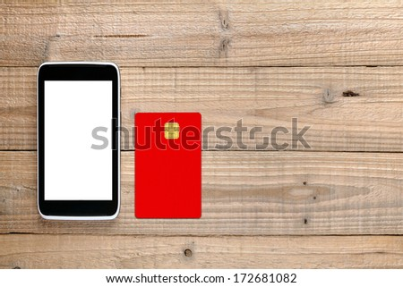 Smartphone and credit card on wooden background - stock photo