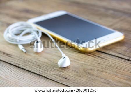 Smartphone and earphones. - stock photo