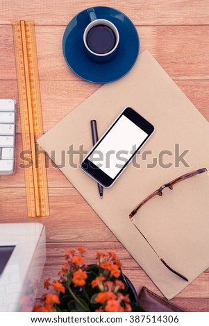 Smartphone and eye glasses on paper by coffee cup at desk in office - stock photo