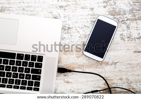 Smartphone and Laptop on a wooden Desktop. - stock photo