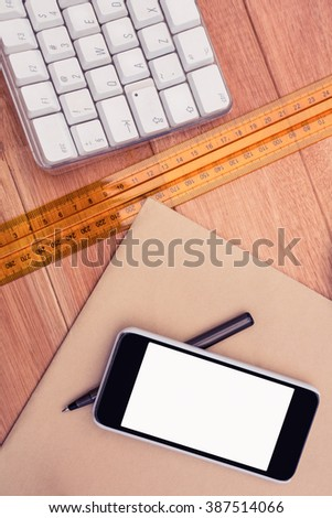 Smartphone and pen on paper by ruler at desk in office - stock photo
