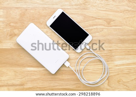 Smartphone charging with power bank on wood board - stock photo
