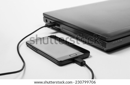 Smartphone connected to a notebook and charging power from it - stock photo