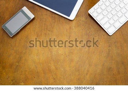 Smartphone, digital tablet and white keyboard on old wooden desk with copyspace