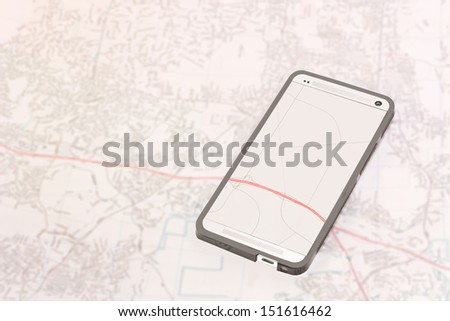 Smartphone gps technology. Cellphone touch screen with road and highway map. Phone display over paper map. Blurry background. Horizontal photo.  - stock photo
