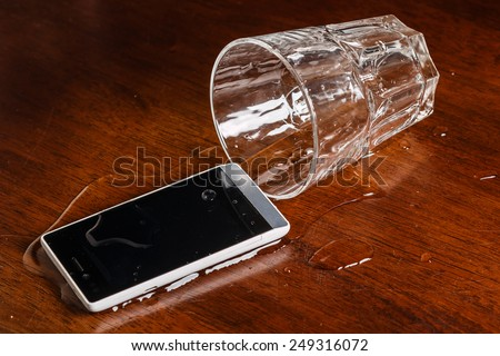 Smartphone in water on the table - stock photo