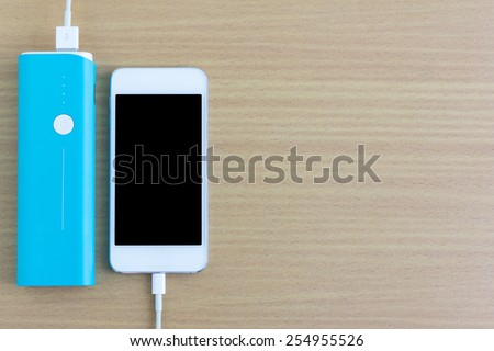 Smartphone is charging with power bank - stock photo