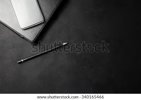 Smartphone Leaning On Tablet close up photo. Electronic devices on black background. - stock photo